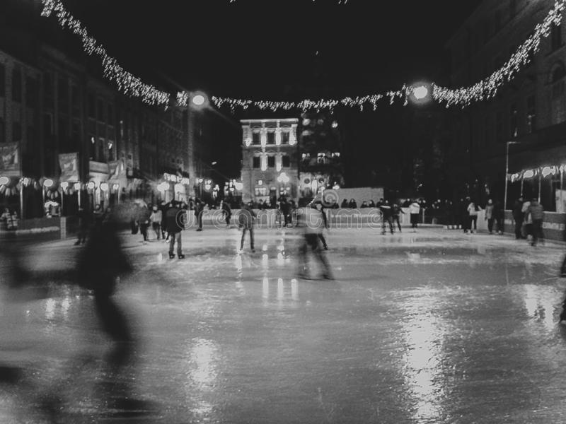 People skating in evening time. Black and white photo royalty free stock images