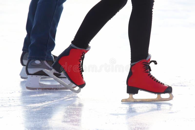 People skating on the ice rink. Raised male handspeople skating on the ice rink stock photo