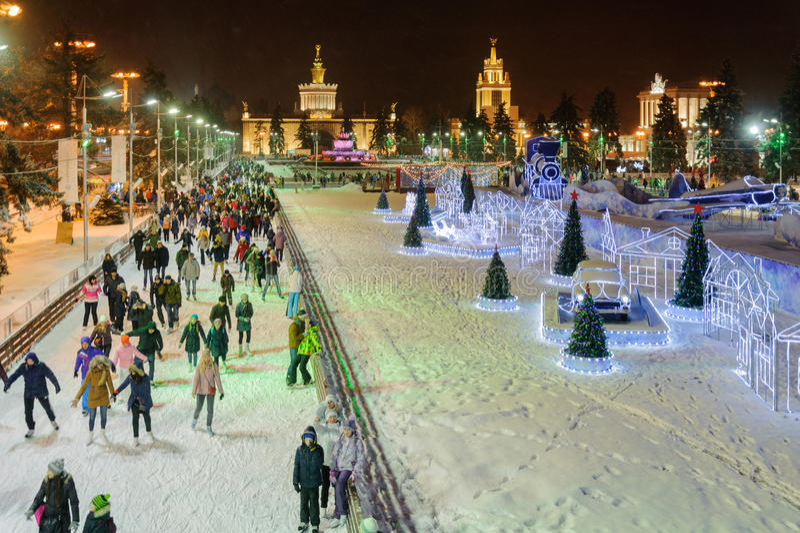 People skating near decorations and illuminations at winter nigh. MOSCOW - JANUARY 4: People skating near decorations and illuminations at VDNKh park at winter stock photo