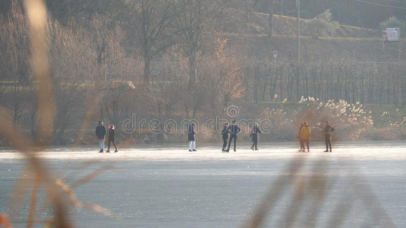 People skating and walking on the frozen lake, fall season royalty free stock photo