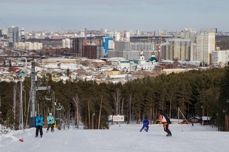 People on the ski slope and view of the city of Yekaterinburg stock images