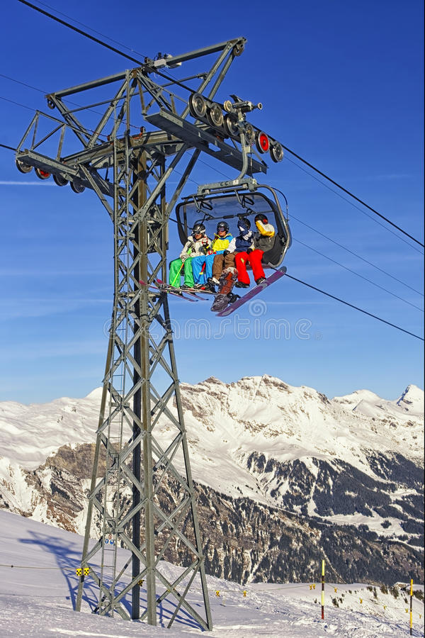 People on ski and snowboards at cable car cabin on winter sport stock images