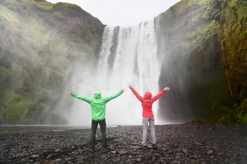 People by Skogafoss waterfall on Iceland. Golden circle. Couple visiting famous tourist attractions and landmarks in Icelandic nature landscape stock photo