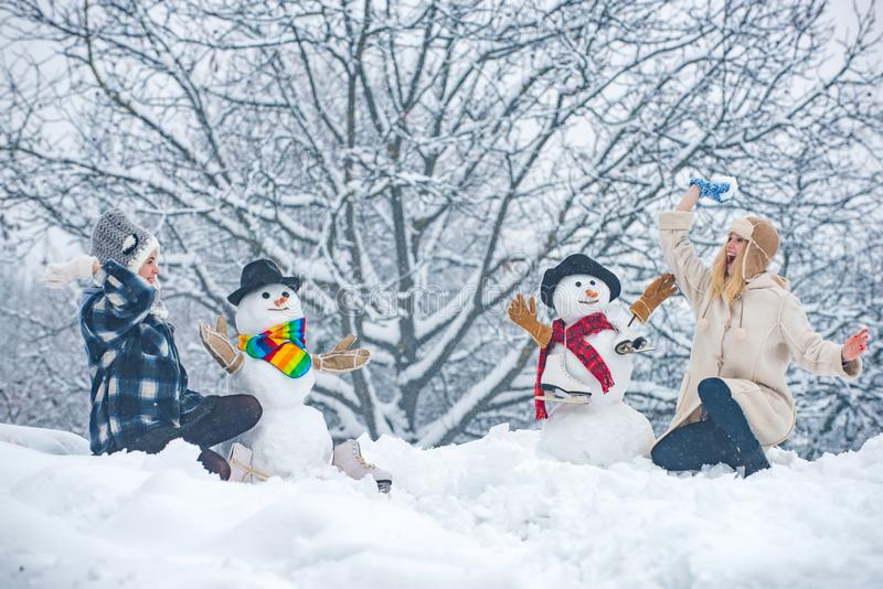 People in snow. Happy smiling girls make snowman on sunny winter day. Two smiling friends make Snowman on Christmas stock photo