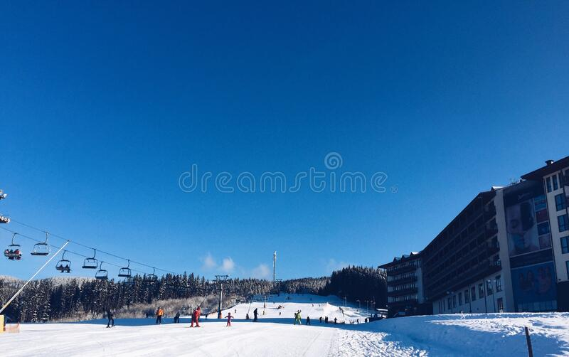 People on a Snowy Ski Hill With a Lift on the Left and a Hotel on the Right royalty free stock photography