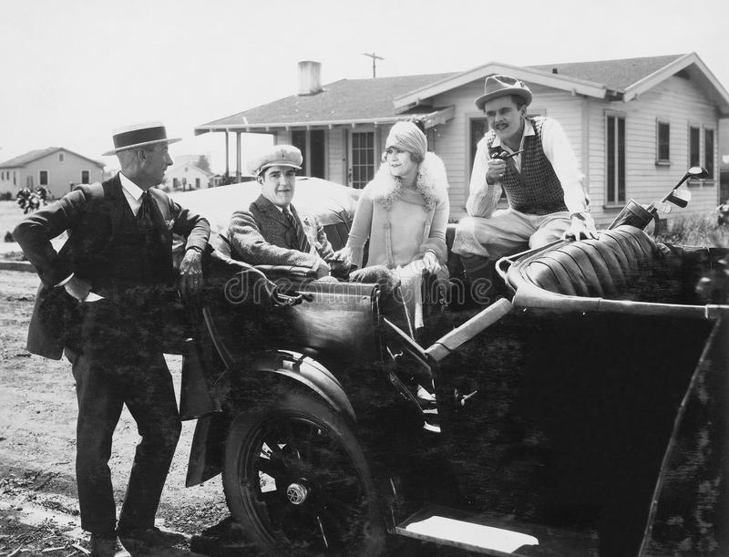 People socializing in parked car. (All persons depicted are no longer living and no estate exists. Supplier grants that there will be no model release issues stock photos