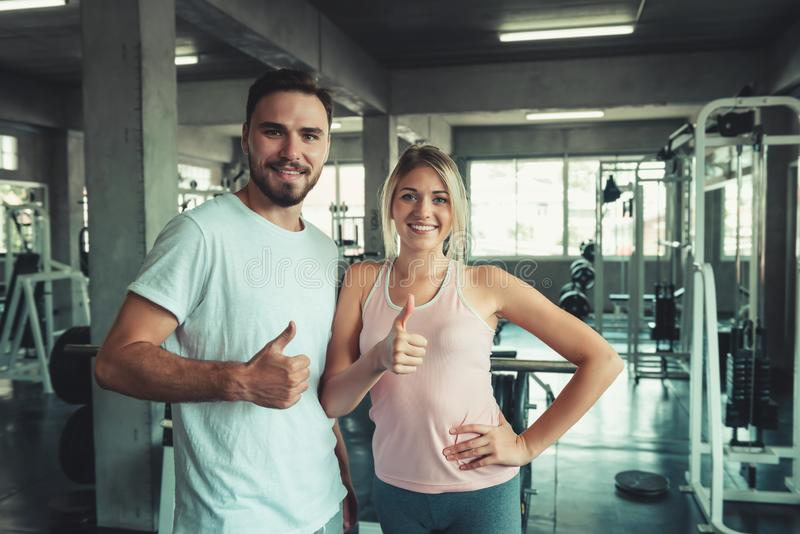 People sport couple concept in fitness gym are giving thumbs up for symbol good health., Portrait of couple in sportswear are stock images