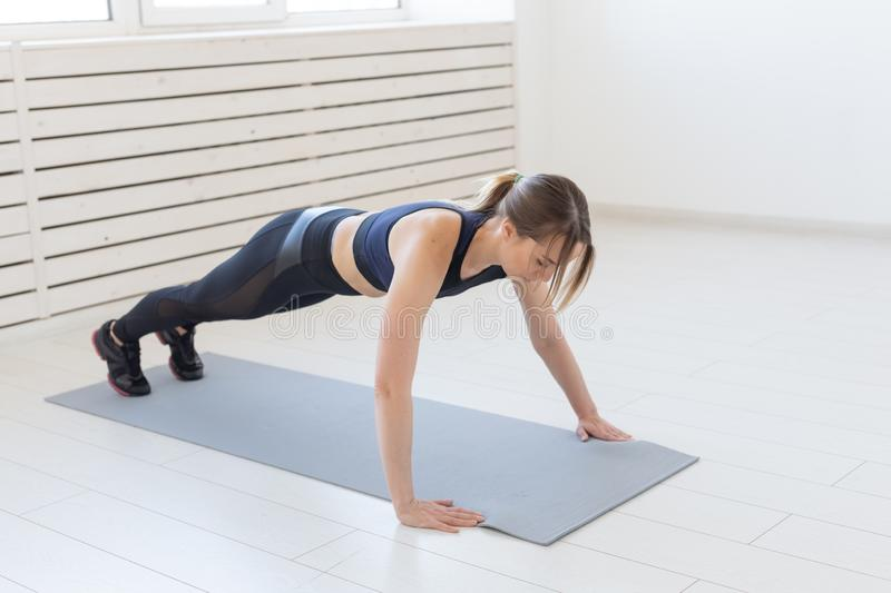 People, sport and fitness concept - young beautiful sportswoman doing push ups.  stock images