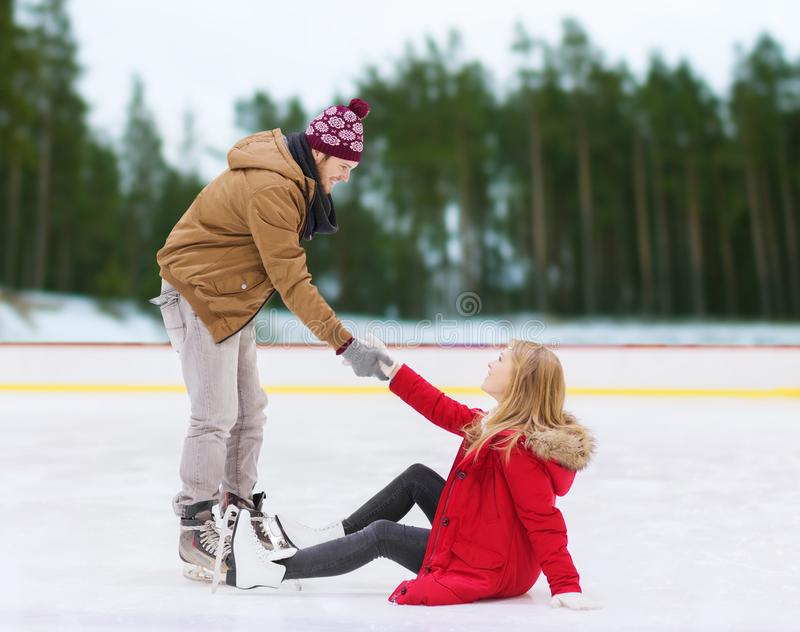 Man helping woman to rise up on skating rink. People, sport and leisure concept - smiling men helping women to rise up on skating rink over winter outdoor royalty free stock photos