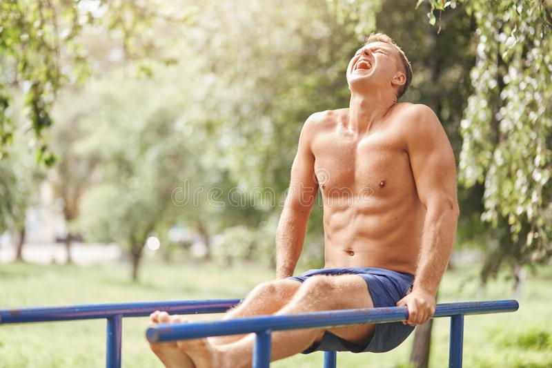 People, sport, motivation concept. Handsome muscular male does exersices outdoor early in morning, wears shorts, works on his arbs royalty free stock photography