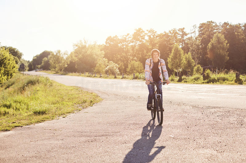 People, sports and healthy active lifestyle concept. Smiling hipster schoolboy with trendy hairdo riding bicycle outdoors. Young c royalty free stock images