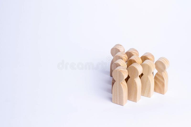 People stand in the formation of the pins. A game of bouwling. Wooden figures of persons, on a white background. The concept of business management personnel royalty free stock images