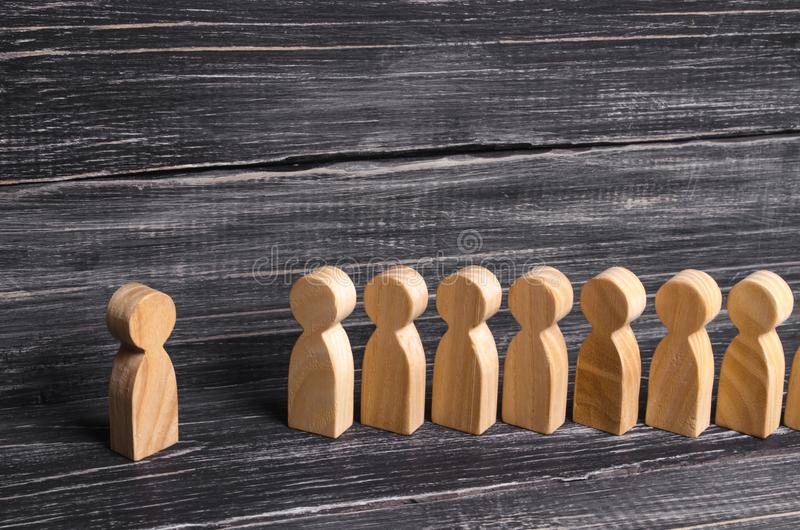 People stand in line at the briefing and wait for orders. Wooden figures of people are waiting in line. Concept of business, army, royalty free stock images