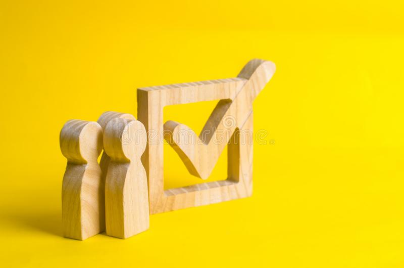 People stand near a wooden checkmark in a box on a yellow background. The concept of suffrage, voting in elections. Election of the President or Government royalty free stock images
