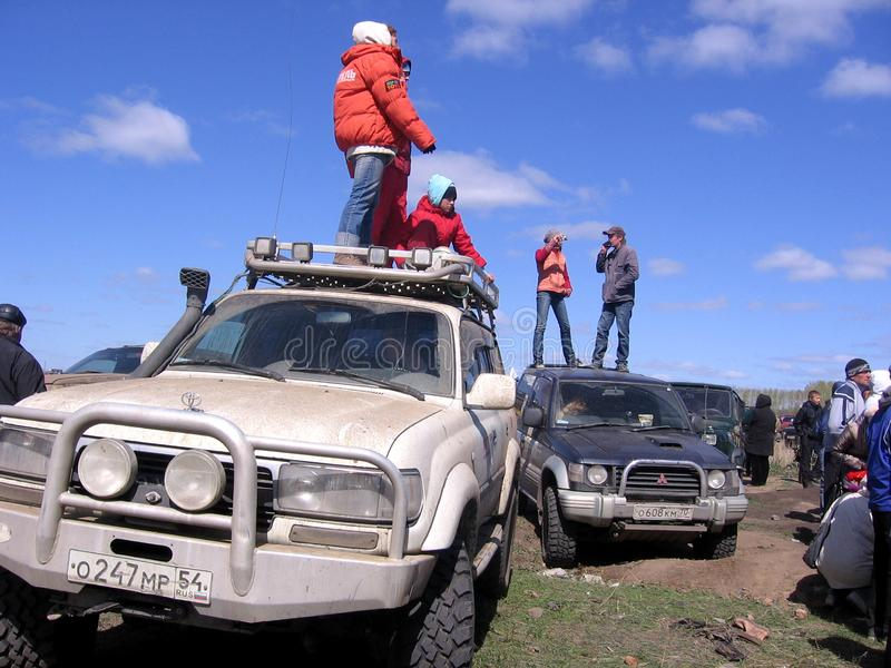 People stand on the roof of the jeeps racing SUVs crowd of spectators watching a stuck car being pushed out of the mud royalty free stock image