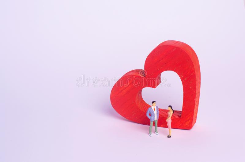 People stand and speak against the background of a red heart. The man is talking to a woman. Live communication, dating. Husband a royalty free stock photos