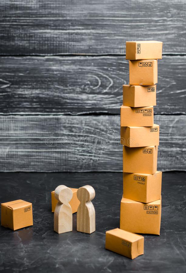 People stand and talk near the tower of cardboard boxes. Concept of business deal, sale of goods. Services for the transportation royalty free stock image