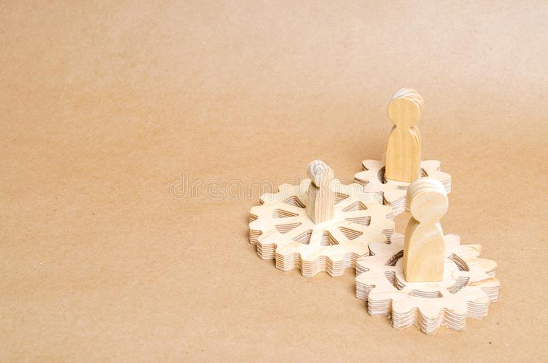 People stand on wooden gears. The concept of technology and industry, the think process. Part of a large complex mechanism. Business process, institution work stock image
