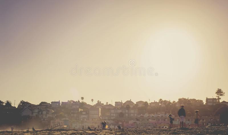 Download People Standing With Buildings In Distance Stock Photo - Image of dawn, sunny: 82984868