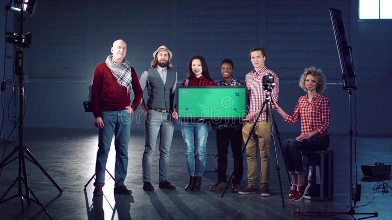 People standing with chromakey board. Cheerful film diverse team posing with a chromakey board royalty free stock image