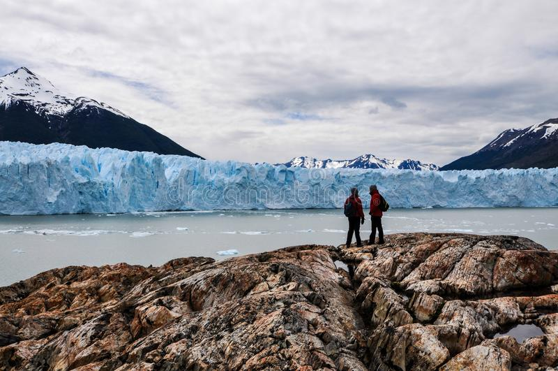 People standing in front of the Perito Moreno glacier. People standing on a roch formation in front of the Perito Moreno glacier in the Argentinean Patagonia stock photography