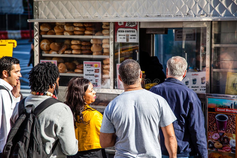 People standing in line at food cart in New York. City stock images