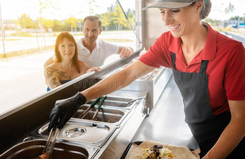 People standing in line in front of food truck stock images