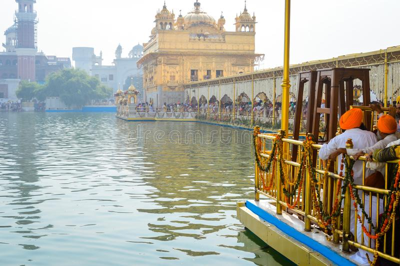 People standing in a row at entrance near Sri Harmandir Sahib or Golden Temple pond, in Amritsar stock photography