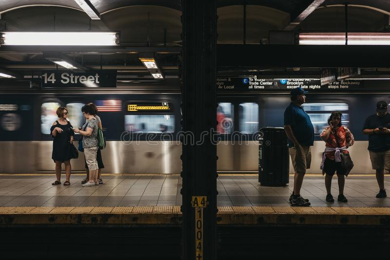 People standing on the 14th Street subway in New York, USA, moving train on the background. stock images