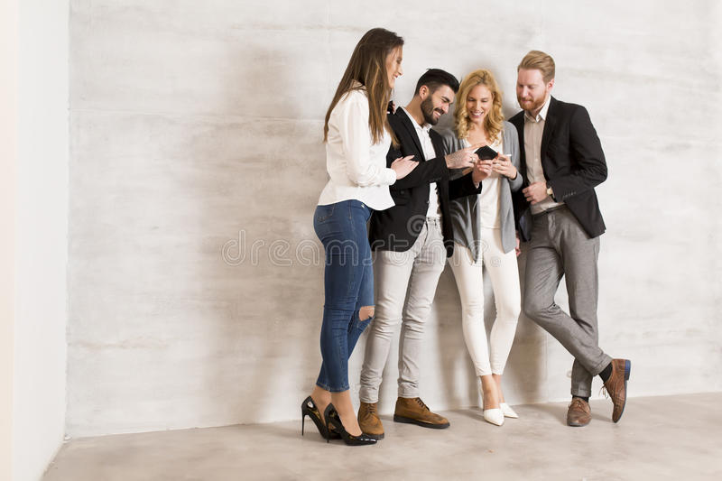 People standing by the wall and keep cell phones in hands stock images