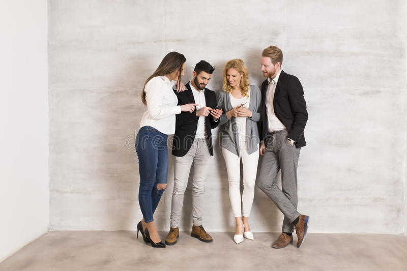 People standing by the wall with mobile phone in hands stock image
