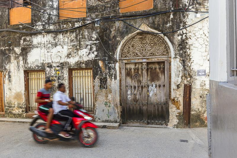 People on the stone town streets and alley-ways. Urban and city life with people and movement on the rustic streets and alley-ways of the old town on zanzibar stock photo