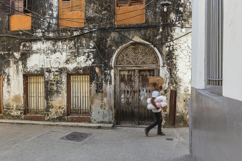 People on the stone town streets and alley-ways. Urban and city life with people and movement on the rustic streets and alley-ways of the old town on zanzibar stock image