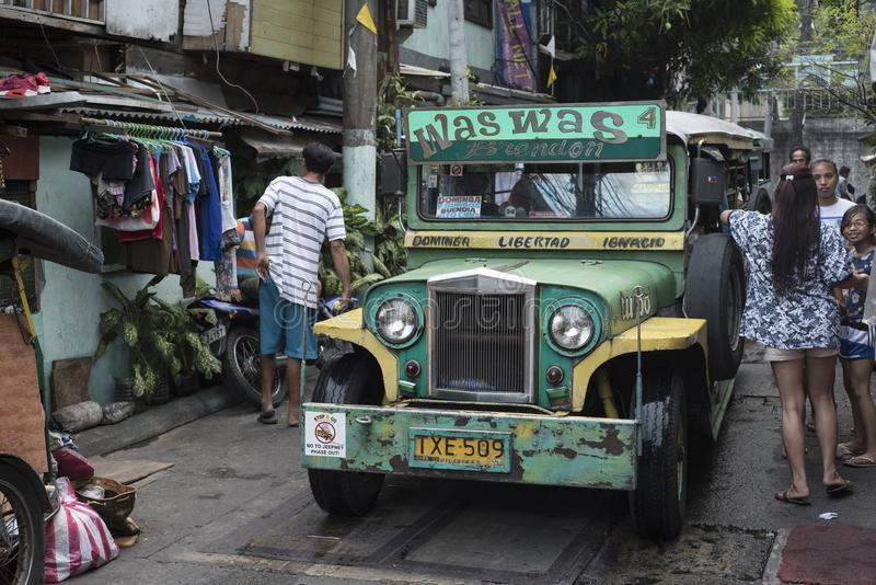 People and a stopped jeepney in a small street of Manila. royalty free stock photography