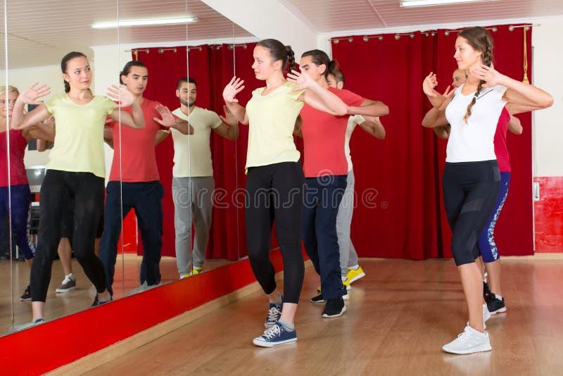 People street dancing in studio. Men and women practicing street dance in a dancing studio royalty free stock photos