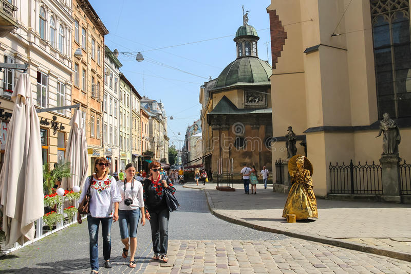 People on street in the Old Town of Lviv, Ukraine. Lviv, Ukraine - July 5, 2014: People near Latin Cathedral (Archcathedral Basilica of the Assumption of the stock photos