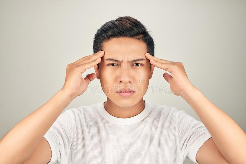 People, stress, tension and migraine concept. Upset unhappy young man squeezing head with hands, suffering from headache royalty free stock photo