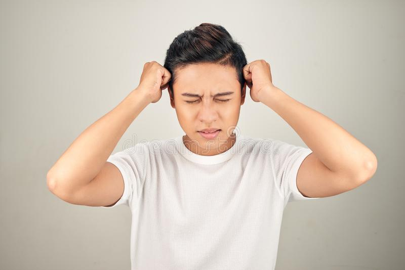 People, stress, tension and migraine concept. Upset unhappy young man squeezing head with hands, suffering from headache royalty free stock image