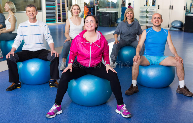 People stretching on fitness balls. Seniors people stretching in a gym on fitness balls stock image