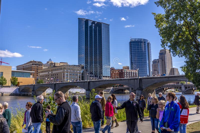 People stroll along the Grand River with Grand Rapids skyline stock photo