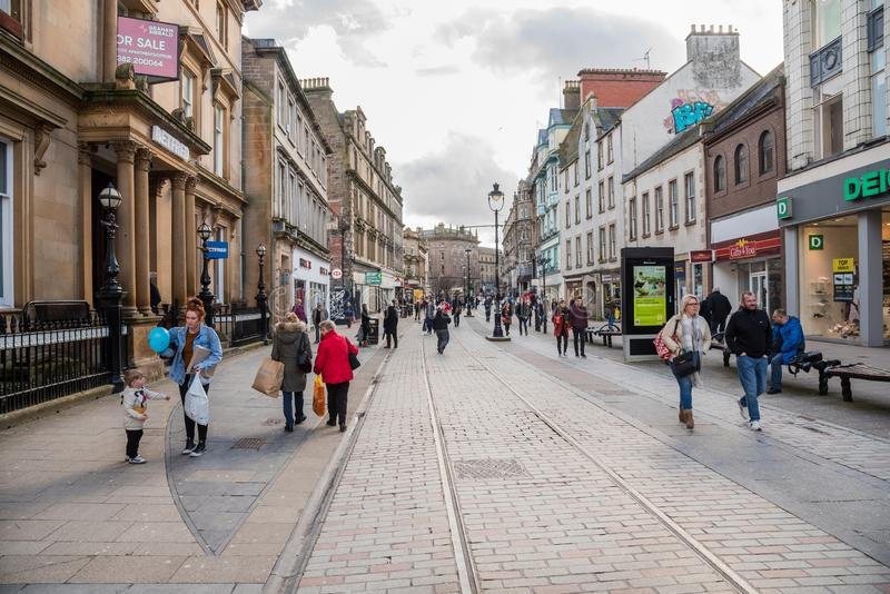 People strolling along a shopping street in central Dundee stock photos