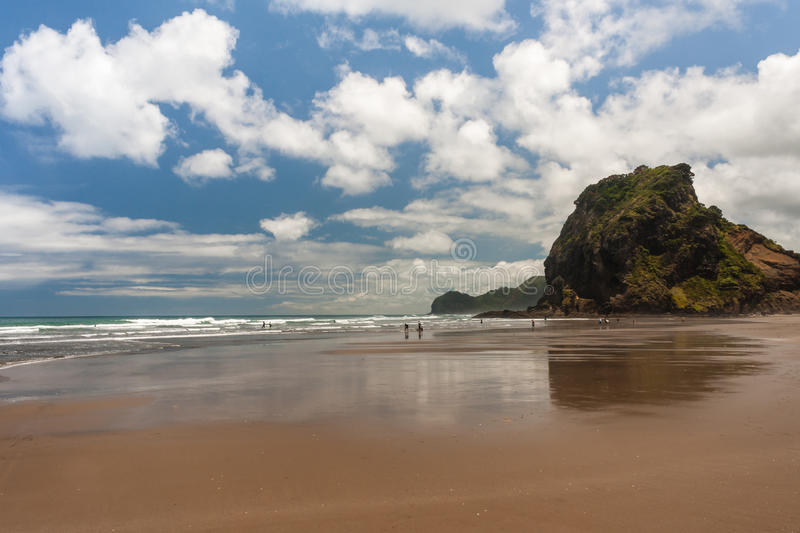 People strolling on Piha beach. In New Zealand royalty free stock photo