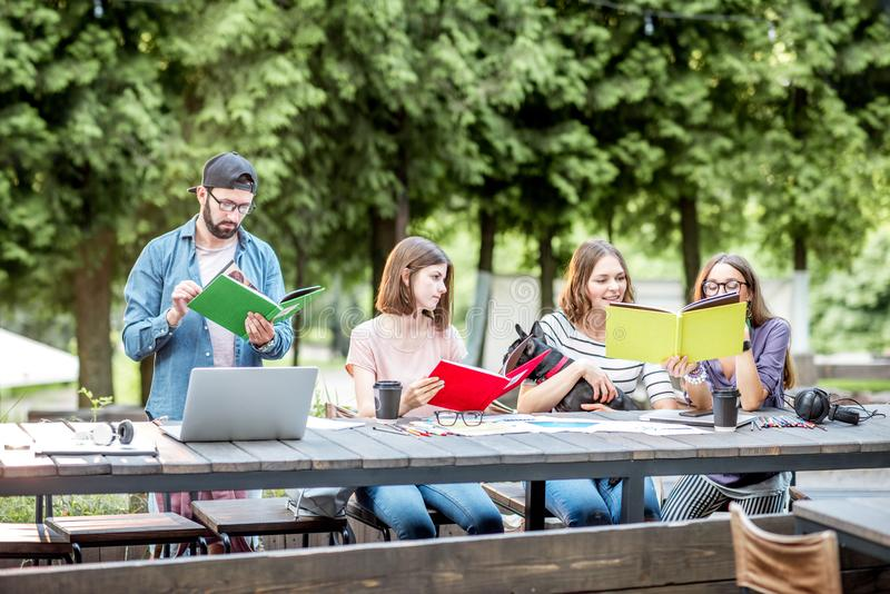 People studying together at the table outdoors. Young friends dressed casually studying with colorful books sitting at the table outdoors in the park stock photo