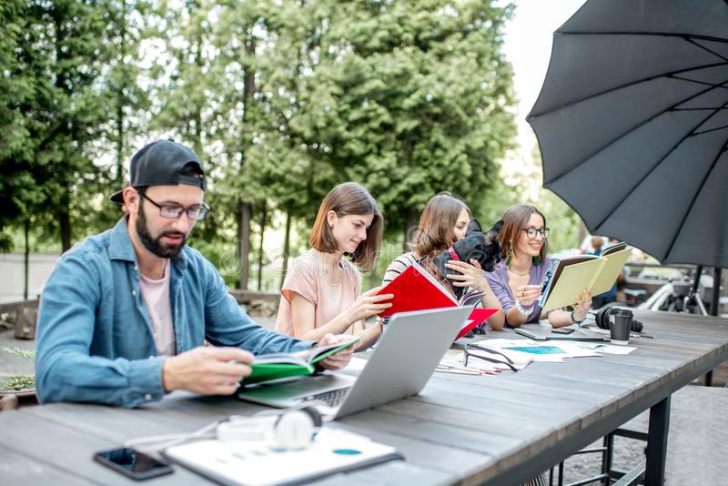 People studying together at the table outdoors. Young friends dressed casually studying with colorful books sitting at the table outdoors in the park royalty free stock photography