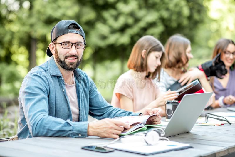 People studying together at the table outdoors. Young friends dressed casually studying with colorful books sitting at the table outdoors in the park royalty free stock photo