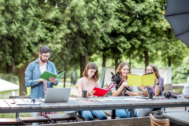 People studying together at the table outdoors. Young friends dressed casually studying with colorful books sitting at the table outdoors in the park stock image