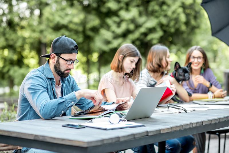 People studying together at the table outdoors. Young friends dressed casually studying with colorful books sitting at the table outdoors in the park stock photography