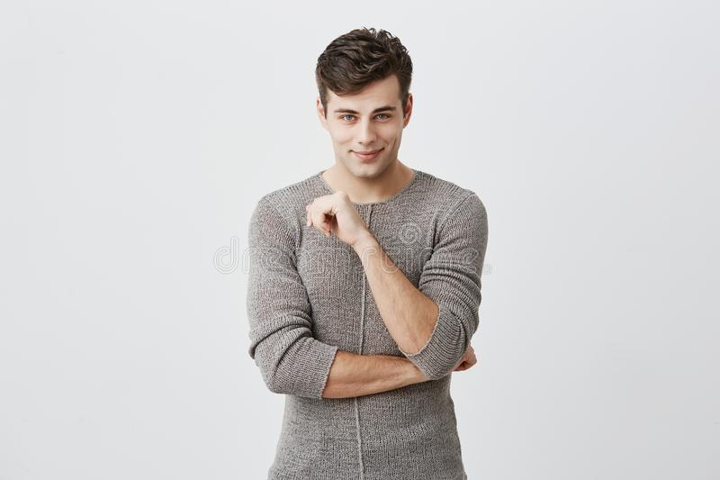 People, style, fashion concept. Handsome young European male with stylish haircut and blue eyes, wearing sweater posing royalty free stock photos