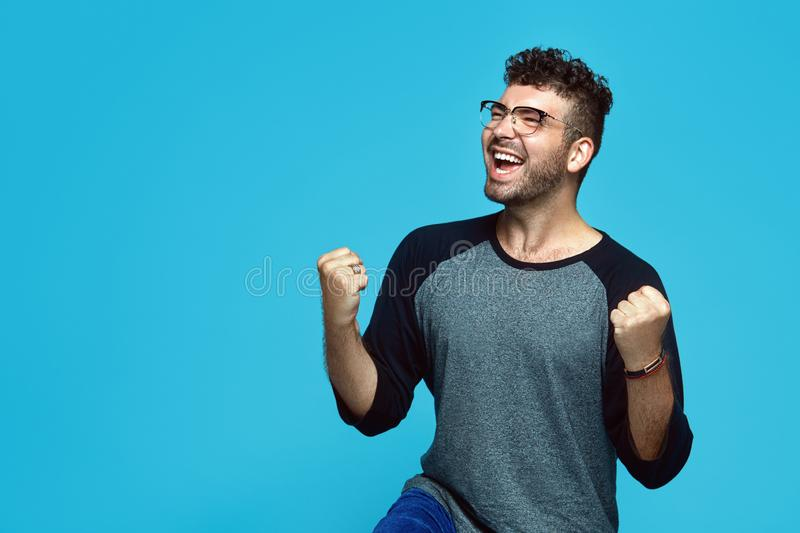 Happy successful young caucasian man screaming Yes and raising clenched fists in the air, feeling excited after he made good deal. stock photos