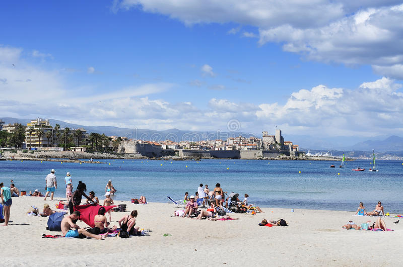 People sunbathing on the beach in Antibes, France. ANTIBES, FRANCE - MAY 15: People sunbathing on the beach on May 15, 2015 in Antibes, France. The fort Chateau royalty free stock images